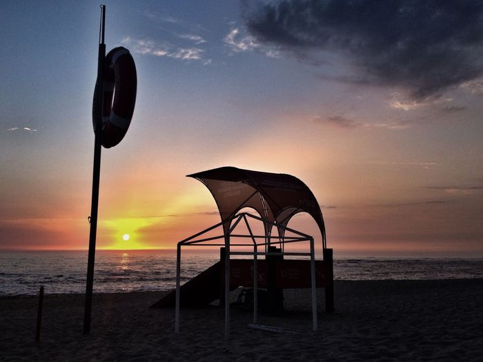 Silhouette lifeguard hut on beach against sky during sunset