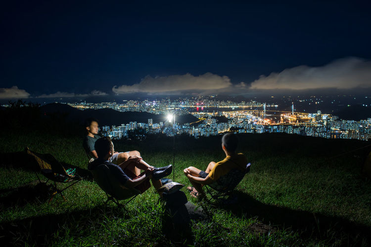 People sitting by illuminated cityscape against sky at night