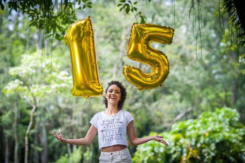 Portrait of smiling teenage girl holding 15 number balloons