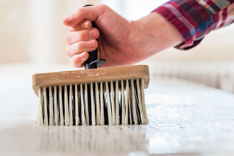 Close-up of make hand holding brush during house renovation