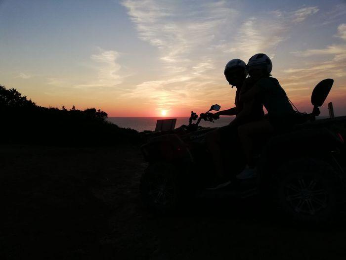 Silhouette men sitting on land against sky during sunset