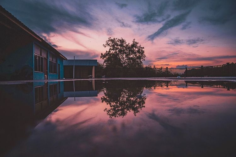 Reflection of trees and house in lake against sky during sunset
