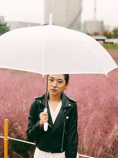 Portrait Of Young Woman Holding Umbrella While Standing Against Field In Rain