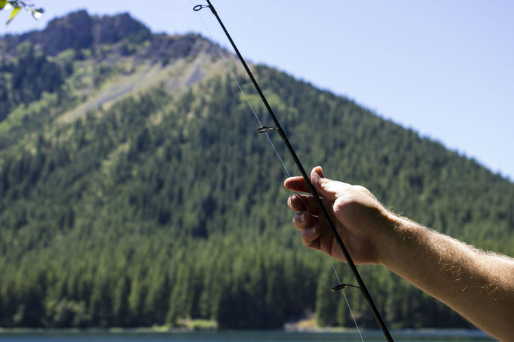 Cropped hand holding fishing rod by lake and mountains