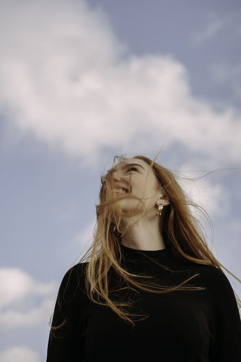 Portrait of a beautiful young woman against sky