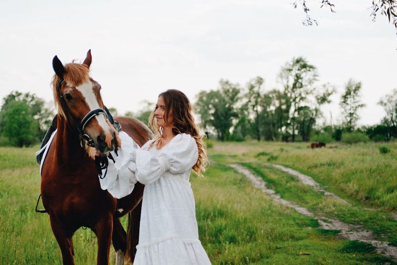 Young woman standing by horse on field