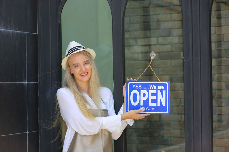 Portrait of a smiling young woman standing against door