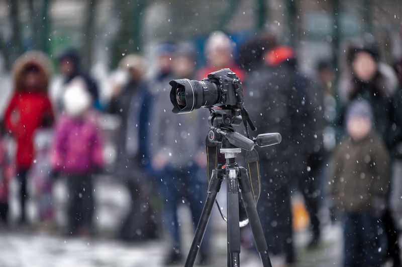 People photographing on snow covered camera