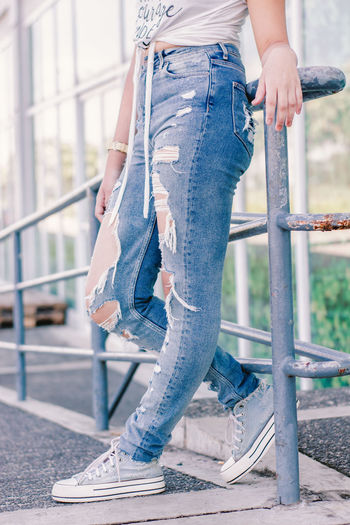 Adult Architecture Built Structure Casual Clothing Day Denim Human Body Part Human Leg Jeans Leisure Activity Lifestyles Low Section One Person Outdoors Railing Real People Standing Textile Women