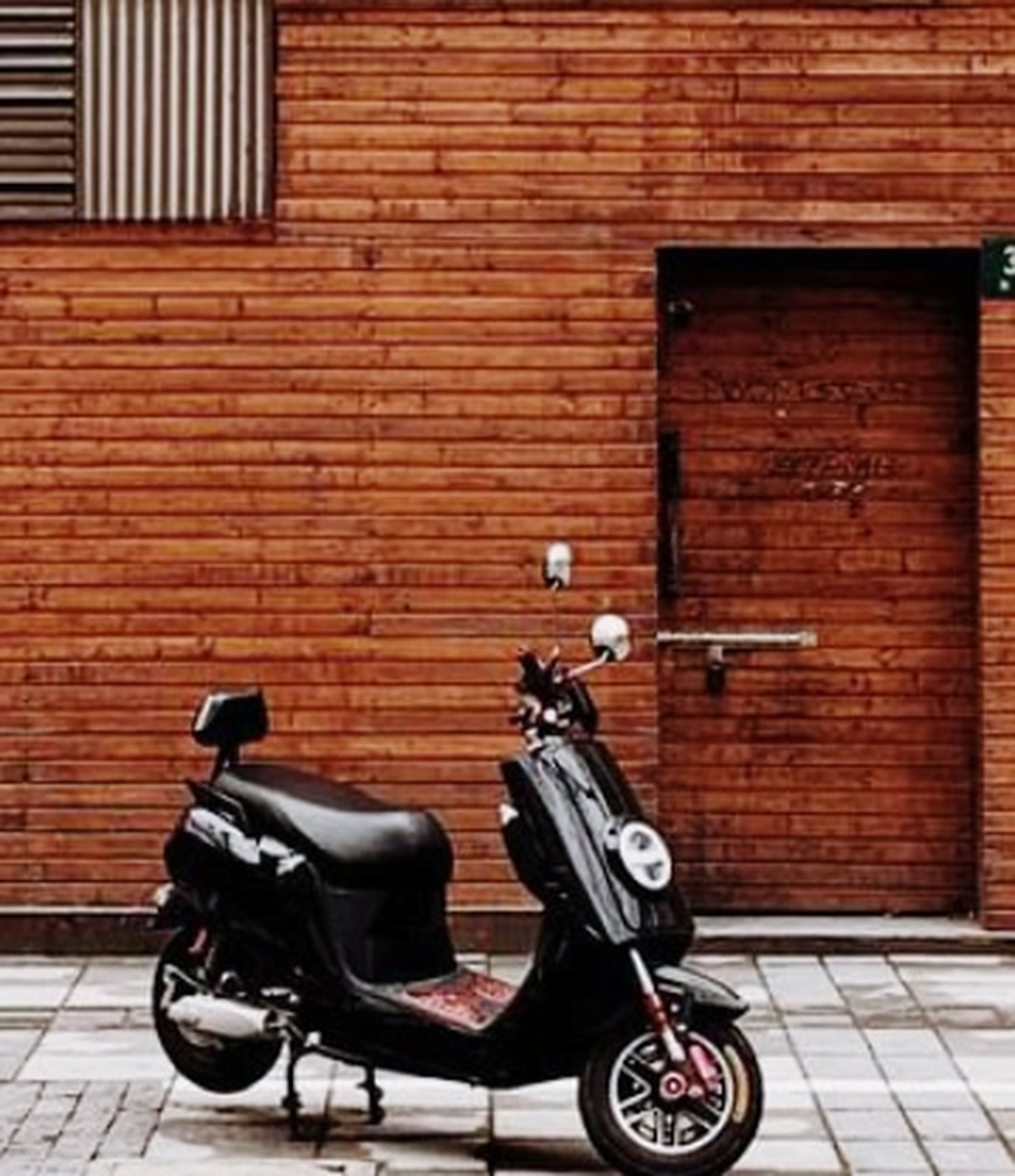 architecture, transportation, building exterior, mode of transportation, brick wall, wall, built structure, brick, city, wall - building feature, vehicle, scooter, land vehicle, no people, day, street, footpath, side view, motor scooter, motorcycle, sidewalk, outdoors, wheel, bicycle