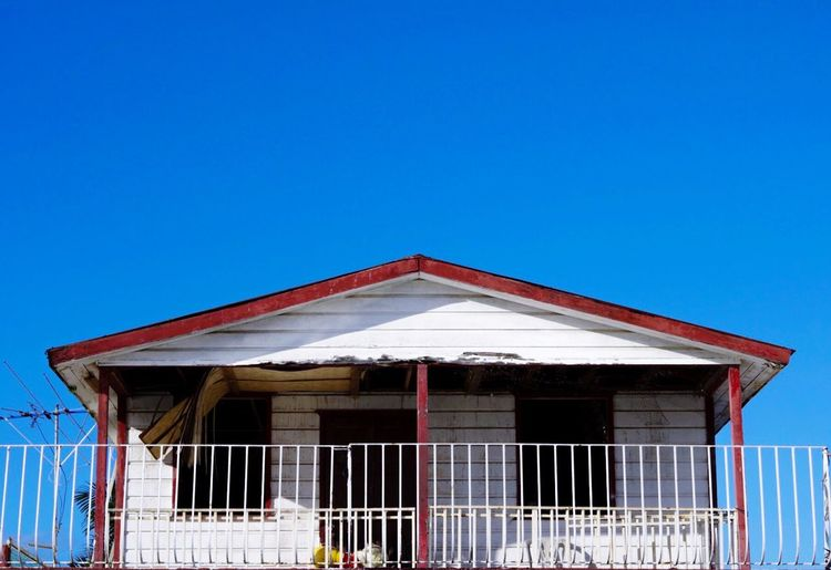 Low Angle View Of Broken House Against Clear Blue Sky