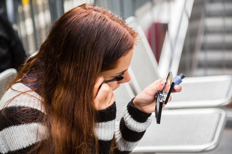 Close-Up Of Woman Applying Mascara While Sitting At Railroad Station