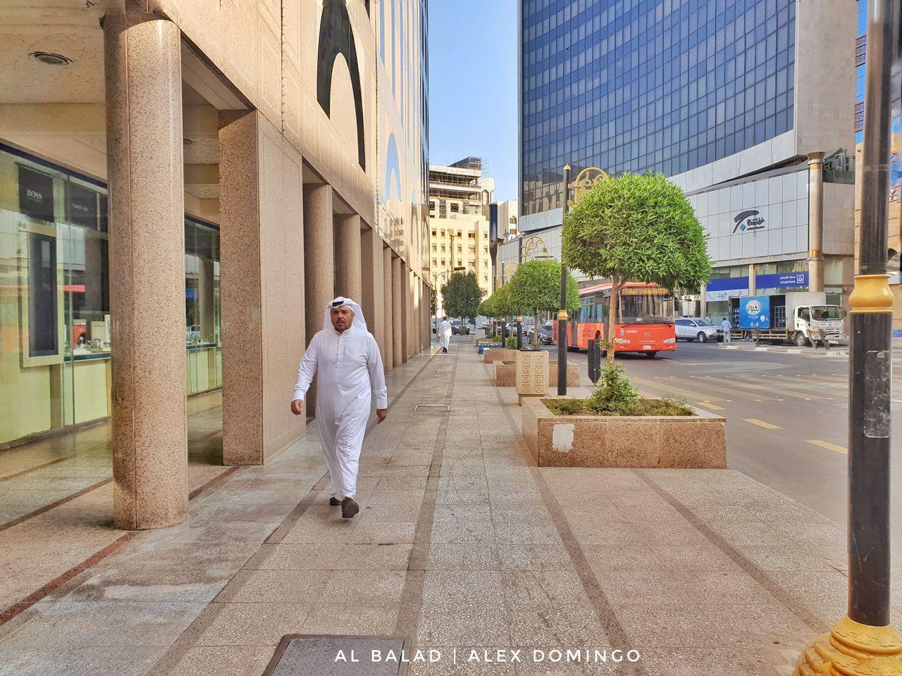 REAR VIEW OF MAN WALKING ON SIDEWALK BY BUILDINGS