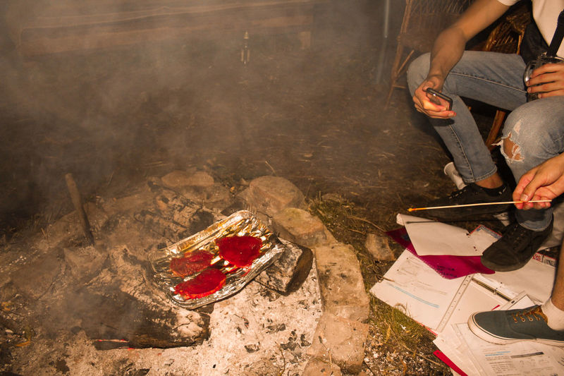 Low section of people sitting by food over fire on land at night