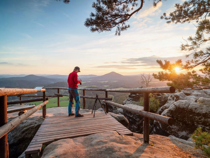 Man standing on railing against mountain during sunset