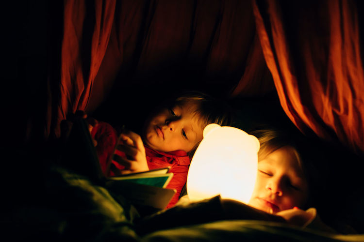 Child reading. kids lying in bed. boy looking at a book while her defocused sister sleeps