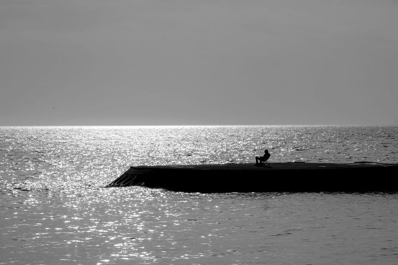 Silhouette man in sea against clear sky