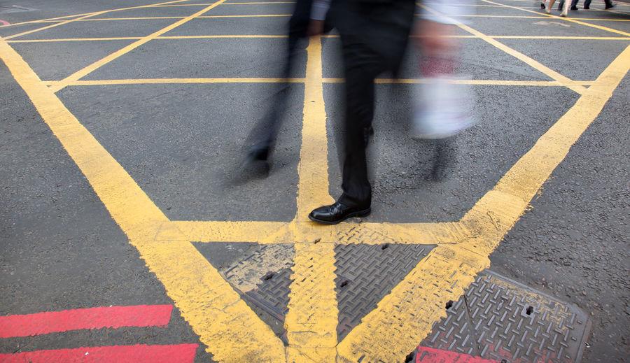 Low section of man walking on zebra crossing in city