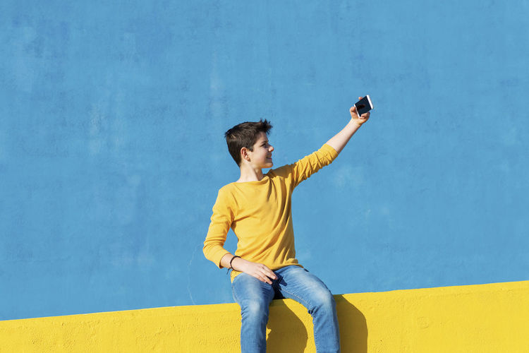 Young man photographing while standing on yellow wall