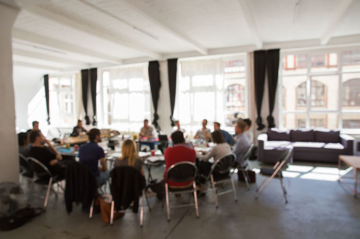 Blurry Business Discussion Group Of People Group Therapy Indoors  Loft Meeting Messy Office Offsite Sitting Table