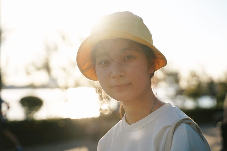 Young asian girl outdoor in the park and wearing bucket hat Portrait Headshot Looking At Camera One Person Focus On Foreground Sunlight Day Real People Lifestyles Nature Leisure Activity Hat Young Adult Front View Lens Flare Back Lit Child Cap Outdoors Teenager Bucket Hat Girl Cute Smiling Sunset Summer Summertime Fashion Asian  Garden Wearing