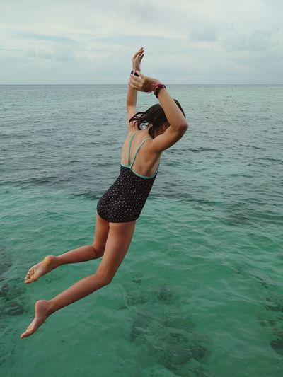 High angle view of girl jumping in sea
