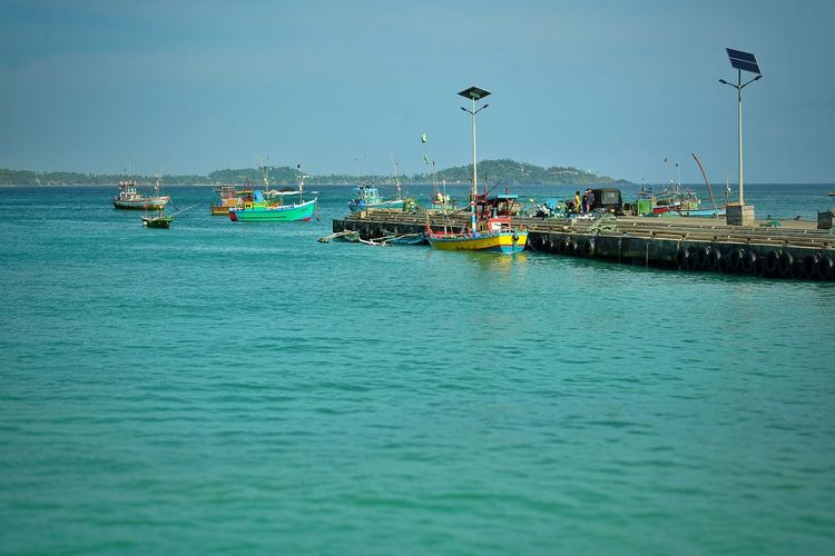 Nautical Vessel Transportation Water Mode Of Transportation Waterfront Sea Sky Nature Day Scenics - Nature Travel Beauty In Nature Outdoors Incidental People Clear Sky Tranquil Scene Tranquility Blue Moored Fishing Boat Passenger Craft Fishing Industry