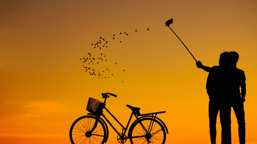 Silhouette of couple taking selfie with bicycle against sky during sunset