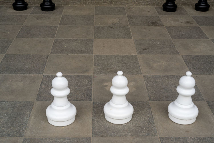 High angle view of chess pieces on tiled floor