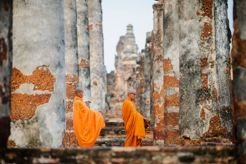 Monks wearing traditional clothing standing at temple
