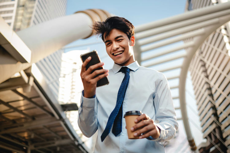Low angle view of man wearing tie using smart phone while holding coffee outdoors