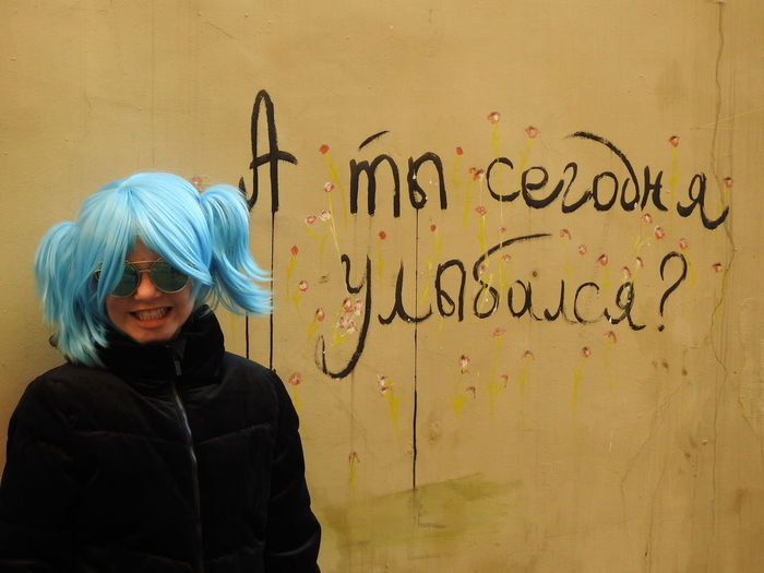Portrait of girl standing against wall with text