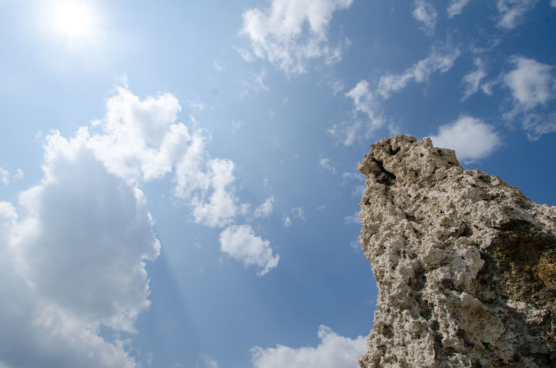 Low angle view of rock formation against sky on sunny day