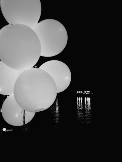 Low angle view of balloons against sky at night