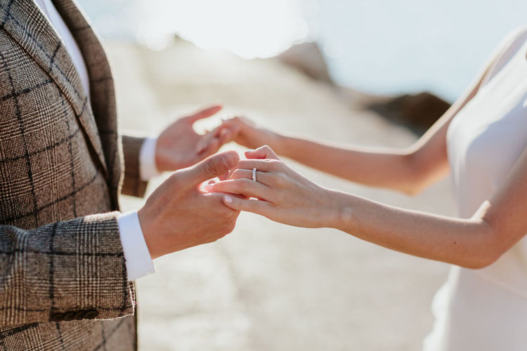 Midsection Of Bride And Groom Holding Hands While Standing Outdoors