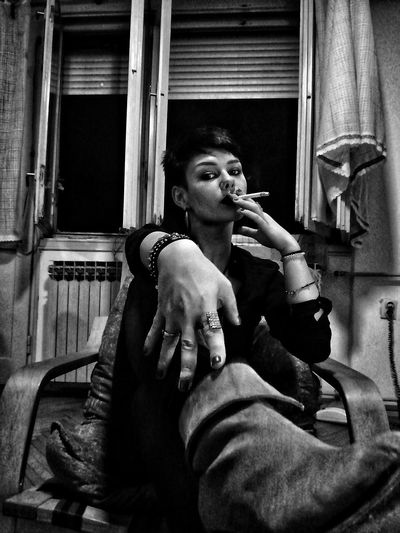 Woman holding cigarette while sitting at home