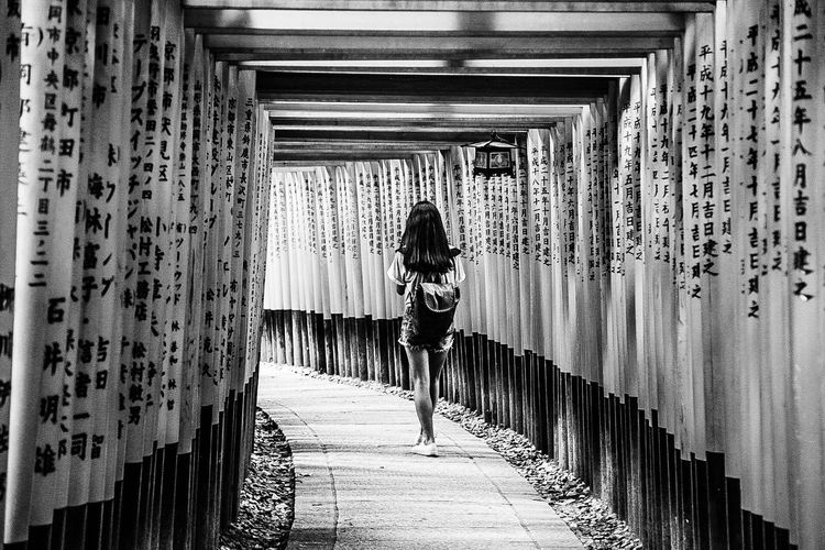 Rear View Of Woman Walking At Fushimi Inari-Taisha