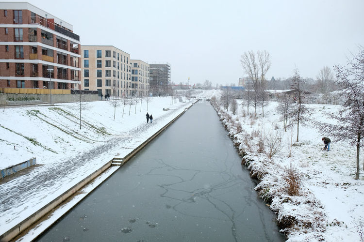 Snow covered road by canal against clear sky