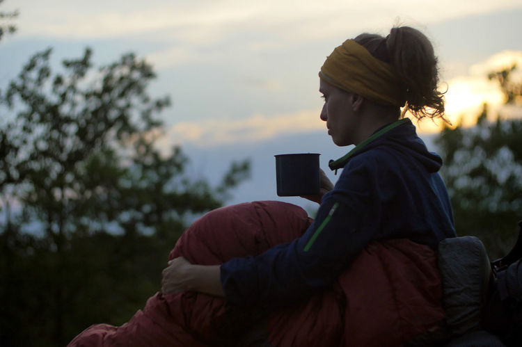 caucasian female hiker drinking beverage from cup while wild camping outdoors Backpacking Camping Coffee Expedition Hiking Hydration Nature Tea Travel Trekking Woman Adult Casual Clothing Caucasian Cozy Drinking Female Focus On Foreground Girl Hairstyle Holding Leisure Activity Lifestyles Nature One Person Outdoors Outside People Plant Portrait Real People Relaxation Side View Sitting Sky Sleeping Bag Technology Three Quarter Length Warm Clothing Wireless Technology Women