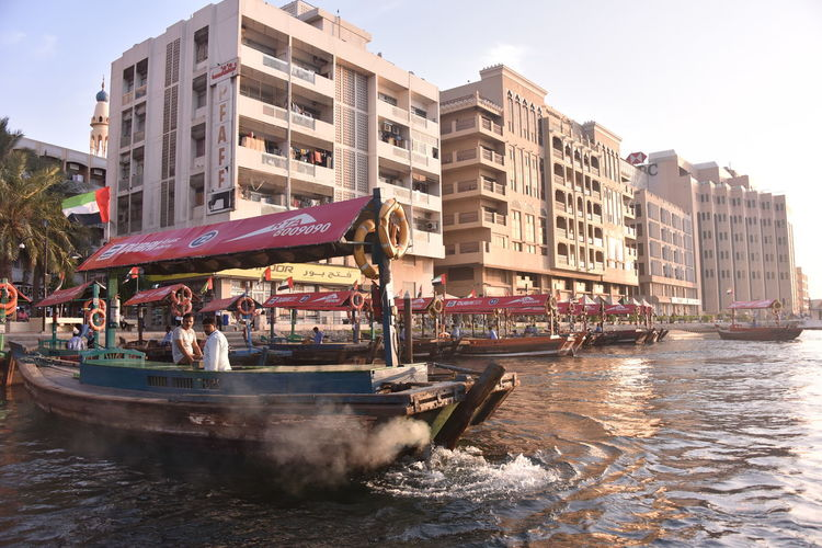 Boats in river against buildings in city
