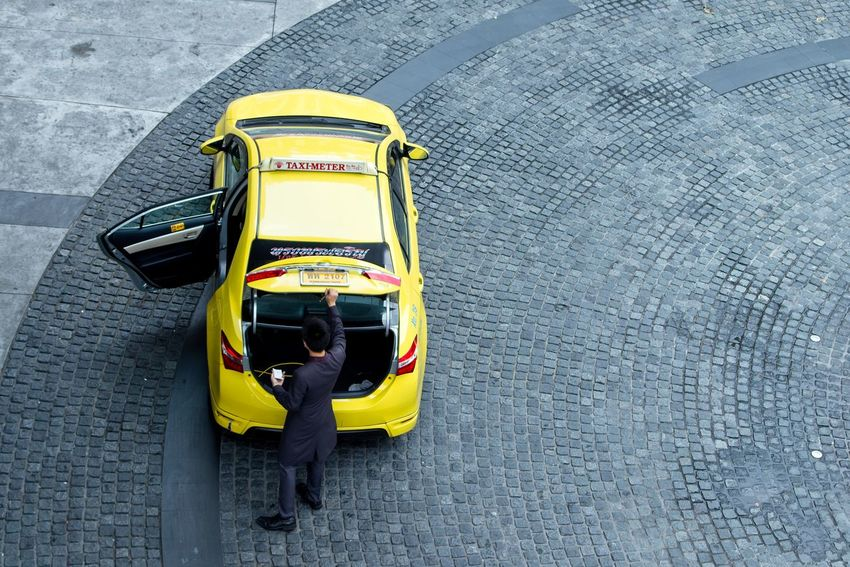 A high angle view of a man opening a boot of a yellow taxi cab in Bangkok, Thailand. Bangkok Man Service Thailand Cab City High Angle View Hotel Hotel Service Jobs Mode Of Transportation Occupation One Person Real People Tourism Destination Transfer Transportation Travel Unrecognizable Person Yellow Yellow Taxi