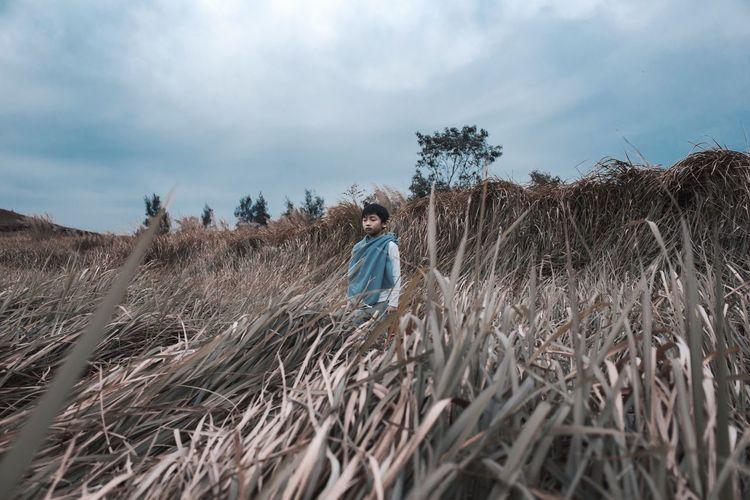 Girl standing on field against sky