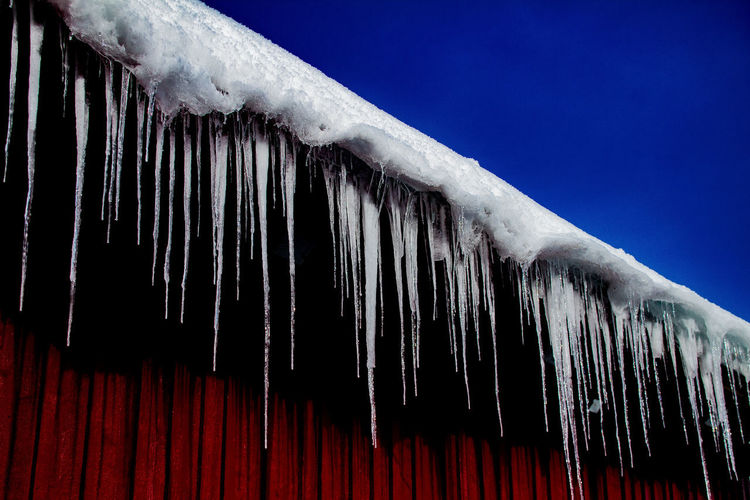 Low angle view of icicles on roof against clear sky