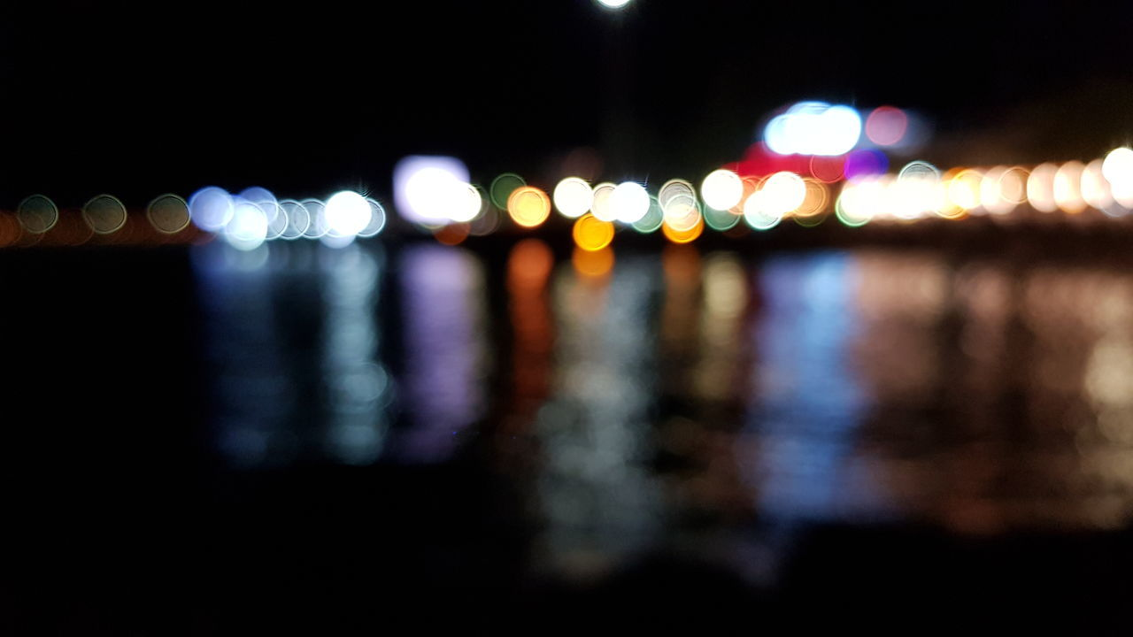 illuminated, night, defocused, lighting equipment, light - natural phenomenon, no people, glowing, multi colored, city, light, lens flare, architecture, reflection, focus on foreground, outdoors, street, water, pattern, built structure, transportation, nightlife