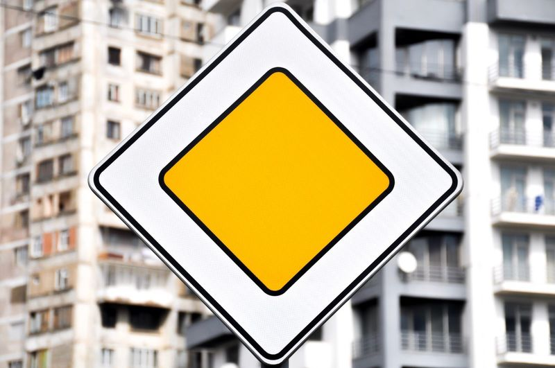 Close-up of yellow sign on metal in city