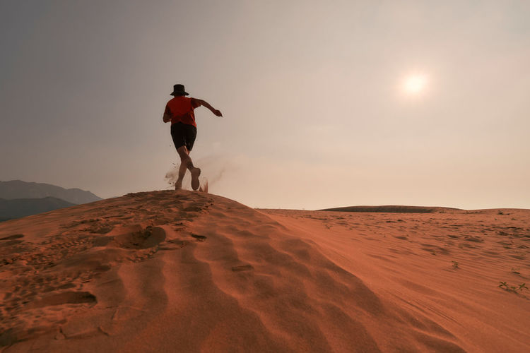 Rear view of man running on sand dune at desert
