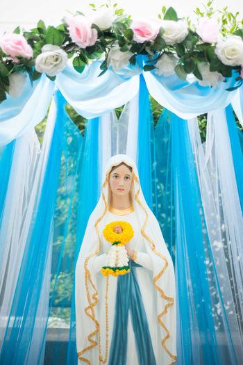 Virgin Mary Statue Against Curtain