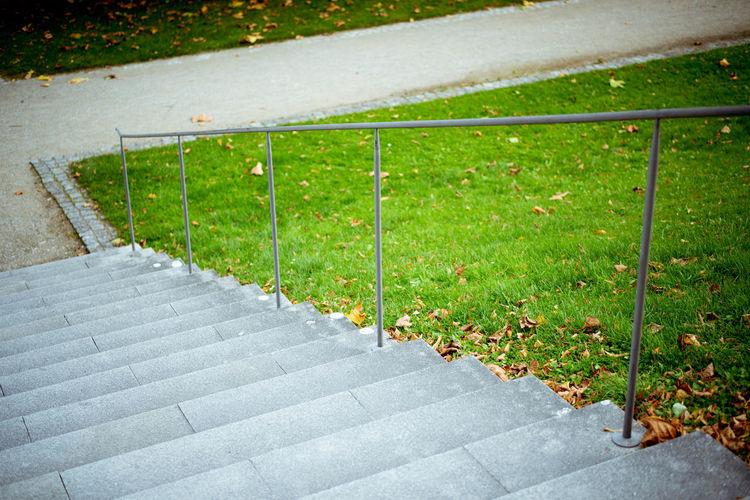 Empty footpath by railing in city