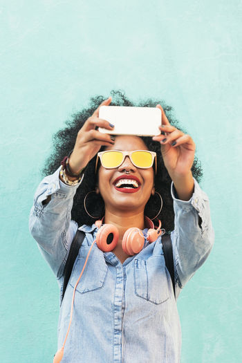 Self portrait of beautiful young afro american Concept. Adult African Afro American Cellphone City Copy Space Headphones Lifestyle Woman Black Cellphone Ethnic Girl Mobile Outdoors Photo Photography Picture Portrait Pretty Selfie Smart Phone Smiling Sunglasses