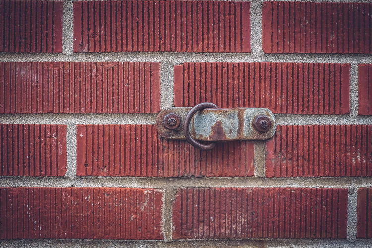 Close-up of metal hook on brick wall